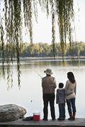 Family fishing off a dock at lake - stock photo