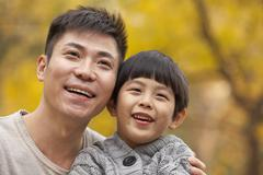 Father and son smiling in the park in autumn, close-up portrait Stock Photos