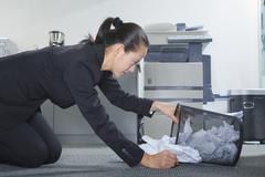 Businesswoman Looking for Papers in Trashcan - stock photo