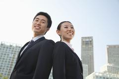 Portrait of two young business people outside in the business district, Beijing, - stock photo