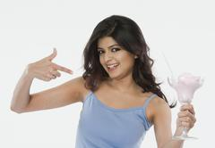 Stock Photo of Portrait of a woman pointing towards an ice cream and smiling