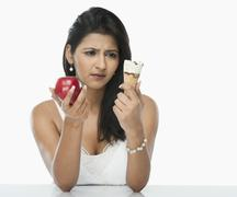 Woman comparing an ice cream cone with an apple Stock Photos