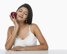 Woman holding an apple and day dreaming - stock photo