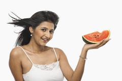 Woman holding a slice of watermelon and laughing Stock Photos