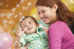 Mother Holding Little Boy While He Plays with Bubbles Stock Photos