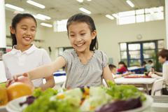 Students reaching for healthy food in school cafeteria Stock Photos