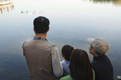 Family looking at ducks in a lake - stock photo