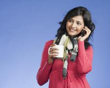 Woman holding a cup of coffee and talking on a mobile phone - stock photo
