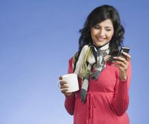 Woman holding a cup of coffee and text messaging on a mobile phone - stock photo