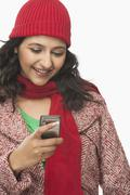 Woman reading a message on a mobile phone and smiling Stock Photos