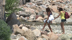 Two teen girls walking on stones. Small river. Stock Footage
