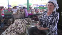 Lady peeling garlic at traditional market in Central Asia Stock Footage
