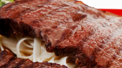 European cuisine : grilled steak with pasta and tomatoes on red plate Stock Footage