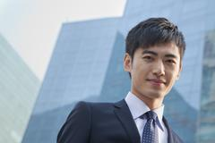 Portrait of young businessman outside glass building Stock Photos