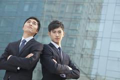 Two young businessmen outside glass building, portrait Stock Photos