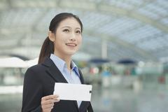 Businesswoman at the airport with airplane ticket - stock photo