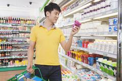 Young Man Looking At Food in Supermarket - stock photo
