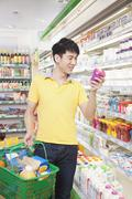 Smiling Young Man Looking At Food in Supermarket - stock photo