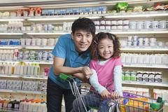 Father and Daughter Shopping in Supermarket, Looking at camera - stock photo