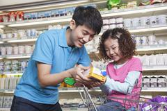 Stock Photo of Father and Daughter Shopping in Supermarket, Looking at Juice Box