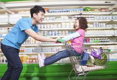 Stock Photo of Father Pushing Daughter in Shopping Cart Inside Supermarket, Laughing
