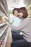 Mother and Daughter in Supermarket Shopping, Kneeling and Looking at a Product - stock photo