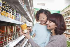 Mother and Daughter in Supermarket Shopping, Looking at a Product - stock photo