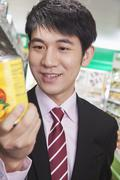 Businessman looking at can in the  Supermarket - stock photo