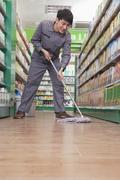 Caretaker Cleaning Floor in Supermarket Stock Photos