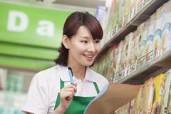 Sales Clerk Checking Groceries in Supermarket - stock photo