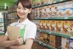 Female Sales Clerk Working in a Supermarket Stock Photos