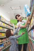 Female Sales Clerk Helping a Little Girl Reach a Cereal Box - stock photo
