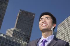 Portrait of young businessman outside in the business district, Beijing - stock photo