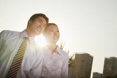 Stock Photo of Portrait of two young business people leaning forward, close-up, brightly lit