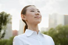 Portrait of smiling young woman outside, eyes closed Stock Photos