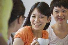 Three Friends sitting and talking in a coffee shop, Beijing - stock photo