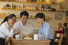 Three friends sitting in coffee shop, looking down at laptop - stock photo
