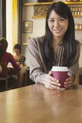 Portrait of young woman holding coffee cup in a coffee shop, Beijing - stock photo