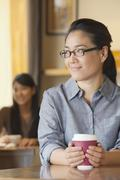 Young woman at coffee shop looking away in contemplation - stock photo