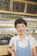 Portrait of smiling young barista in coffee shop, Beijing - stock photo