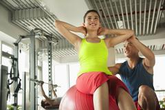 Stock Photo of Young women exercising with her personal trainer in the gym