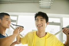 Stock Photo of Young man exercising with his personal trainer in the gym