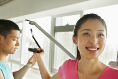 Young woman exercising with his personal trainer in the gym Stock Photos