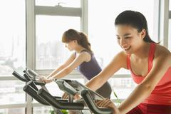 Young women on stationary bikes exercising in the gym - stock photo