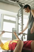 Young men weight lifting with his personal trainer in the gym - stock photo