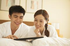 Young Couple Using Tablet in Bed - stock photo