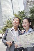 Two young businesswomen with the map looking for location - stock photo