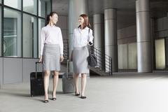 Two young businesswomen walking with suitcases and talking - stock photo