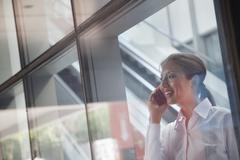 Young businesswoman inside the building talking on the phone and looking through - stock photo
