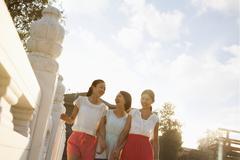 Three Friends Walking Across a Bridge Stock Photos
